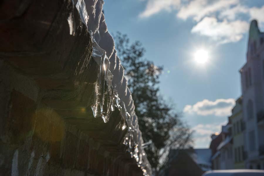 Funkelnde Eiszapfen an der Mauer